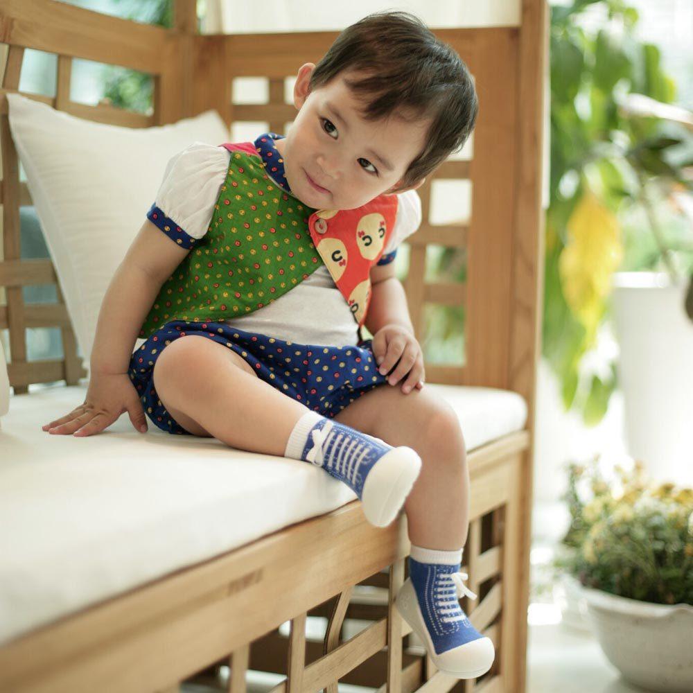 Niño sentado con patucos azules
